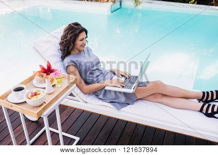 Young woman using laptop near poolside while relaxing on sun lounger