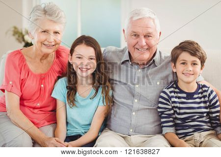 Portrait of grandparents and grandchildren sitting together on sofa in living room