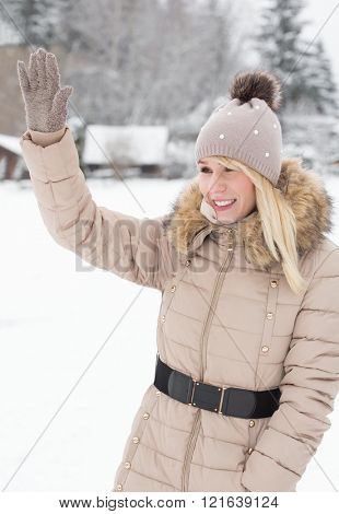 A beautiful young woman standing in a winter landscape and waving a greeting