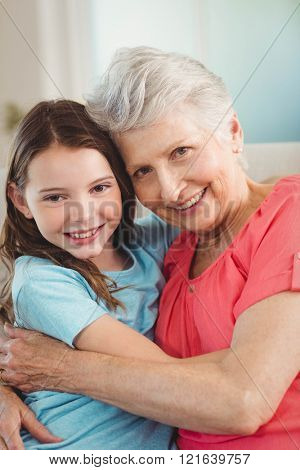 Portrait of grandmother and granddaughter smiling while embracing each other