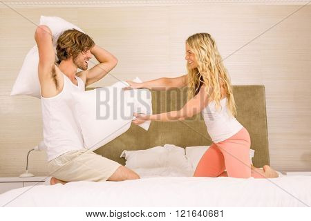 Cute couple pillow fighting on their bed in the bedroom