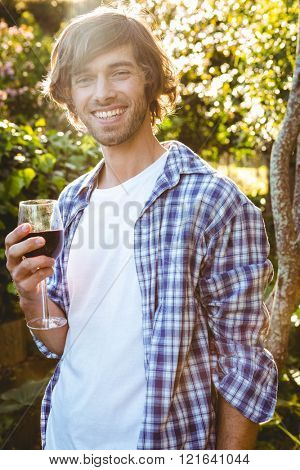 Smiling man with a glass of red wine in the garden