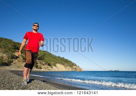 Young athlete running fast jumping over rocks with beautiful sea horizon on background.