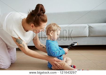 Young Mother With Her One Years Old Little Son Dressed In Pajamas Are Posing. Mom With Son Taking Se