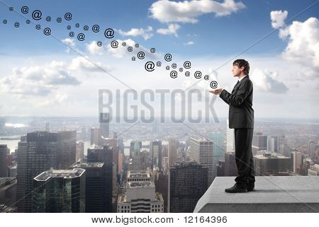 Businessman with at signs flying from his hands on the rooftop of a skyscraper