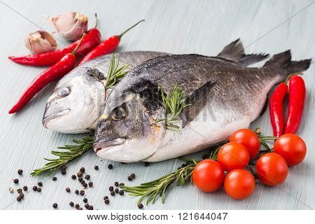 Raw fresh dorado fish with vegetables and spices. Healthy food