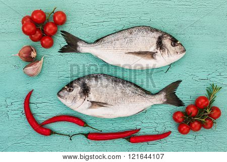 Fresh dorado fish with vegetables on blue table. Copy space top view