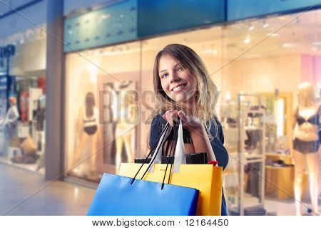 Smiling woman carrying some shopping bags with shops on the background