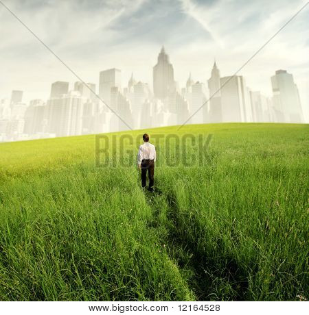Businessman walking on a green meadow with cityscape on the background