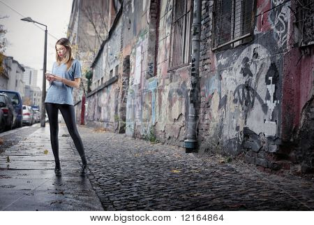 Beautiful young woman using a mobile phone on a city street full of graffiti