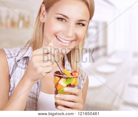 Closeup portrait of beautiful cheerful woman enjoying tasty juice fruits salad, having breakfast at home, healthy eating concept