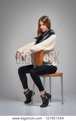 Pretty young adult girl with blond hair posing in the studio with a chair