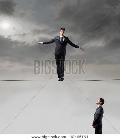 Businessman standing on a rope and other businessman looking at him