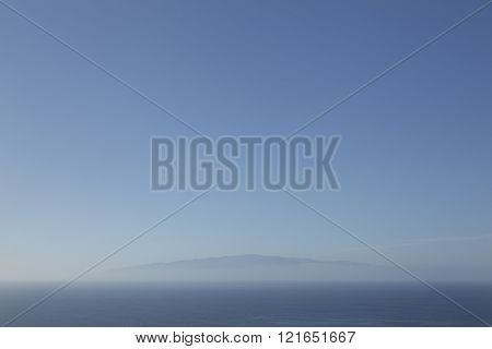 canadian island la gomera seen through the mist from tenerife in blue surroundings of ocean and sky