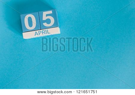 April 5th. Image of april 5 wooden color calendar on blue background.  Spring day, empty space for t