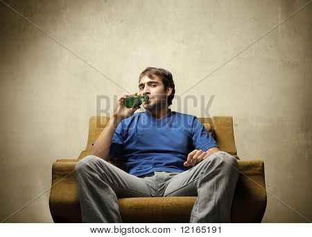 Young man sitting on an armchair and drinking a beer