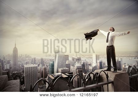 Happy businessman standing on the rooftop of a skyscraper over a cityscape