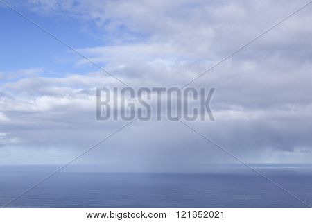 expanse of atlantic ocean north of tenerife and sky with blue part and clouds with distant rain storm