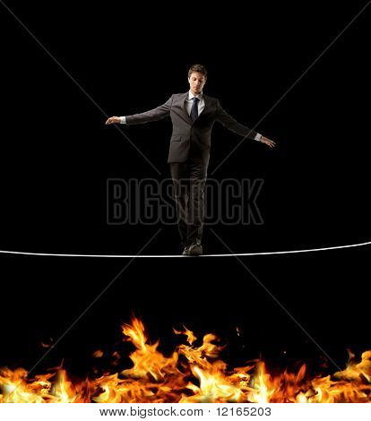 Businessman standing on a rope over a fire