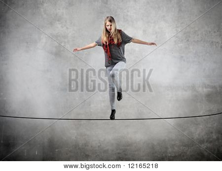 Hermosa mujer de pie sobre una cuerda sobre el vacío