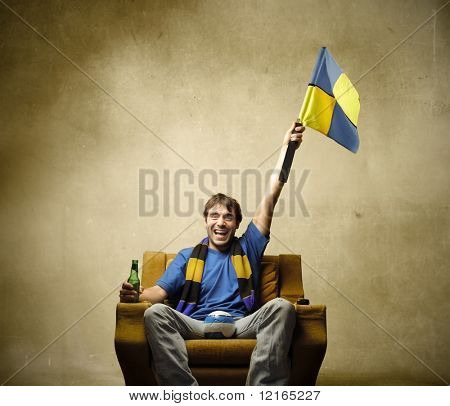 Supporter waving a flag while sitting on an armchair