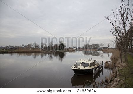 river amstel and small boat in winter not far from Amsterdam near amstelveen and ouderkerk
