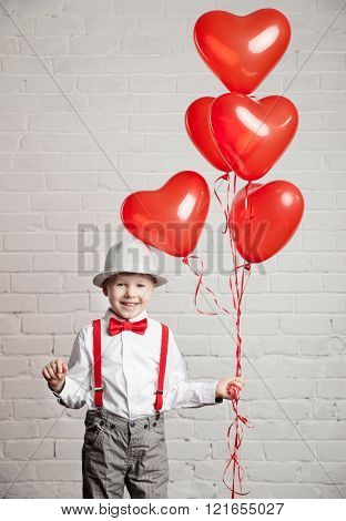Young boy holding a heart-shaped ballon