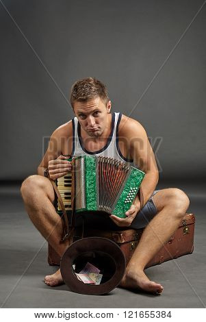 Portrait Of A Man With Accordion Sitting On Retro Suitcase