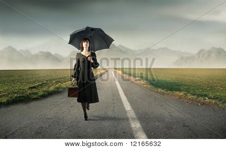 Woman holding a suitcase and an umbrella and walking on a countryside road