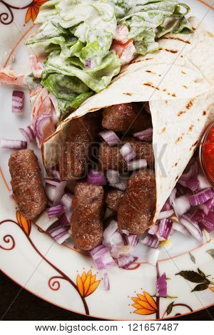 Cevapcici, bosnian minced meat kebab with onion, wrapped in pita bread