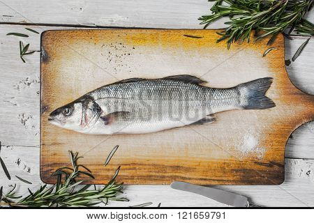 Sea bass with rosemary on the wooden board