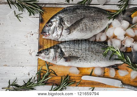 Dorado fish and sea bass with rosemary on the wooden board