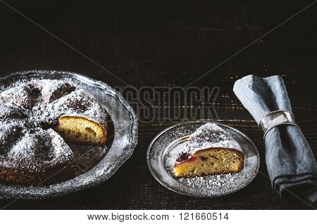 Cake with powdered sugar with a piece cut off with napkin in the vintage ring