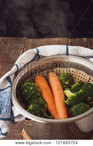 Steamed broccoli and carrots in the pot with steam
