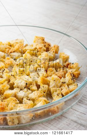 Small croutons with pepper on the glass dish at the left of the table