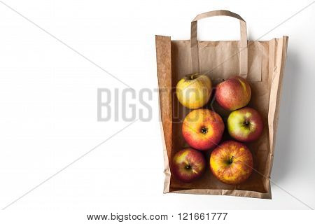 Apples inside a paper bag top view