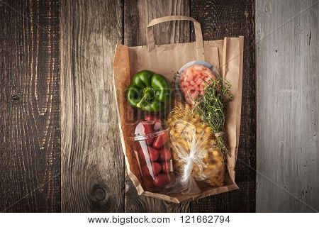 Food mix inside a paper bag on the wooden background horizontal