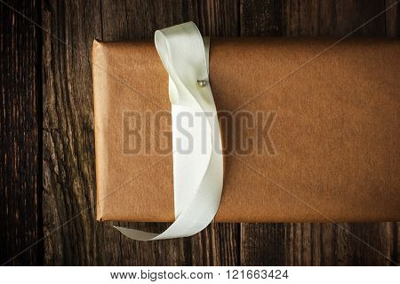 Homemade gift with white ribbon on the wooden background
