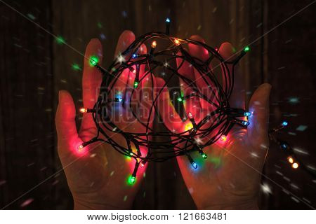 Shining colorful festoon in the hands horizontal