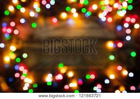 Blurred frame of the colorful Christmas festoon on the wooden board