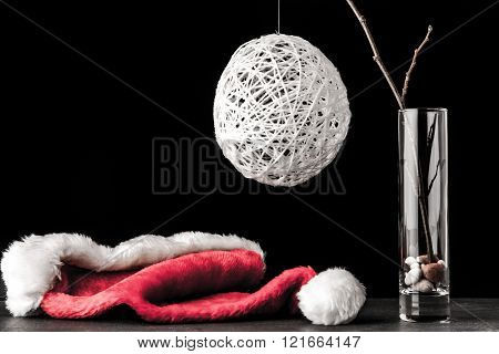 Alder branch in the glass with a white christmas ball and santa claus hat on the black stone table horizontal
