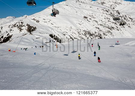 MAYRHOFEN, AUSTRIA :  MARCH 22, 2016:View of  snowboarders in Mayrhofen Ski resort area with ski lifts, pistes and skiers. Zillertal Alps, Tirol.