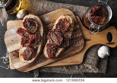 Sun-dried tomatoes on the white bread on the wooden board top-view horizontal