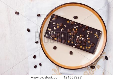 Chocolate with zest and coffee beans on the white table