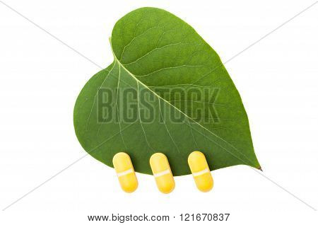 Three Yellow Pills On Green Leaf