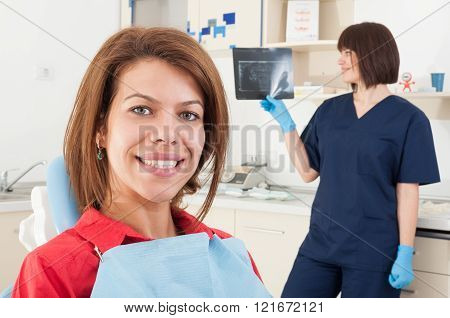 Female patient smiling and woman dentist doctor checking radiography in the background