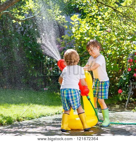 Two little kids playing with garden hose in summer