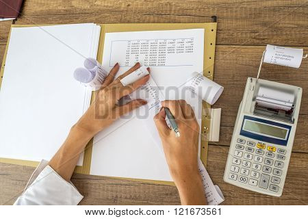 Female accountant or tax adviser working with receipts and statistical  data with calculator on her office desk.