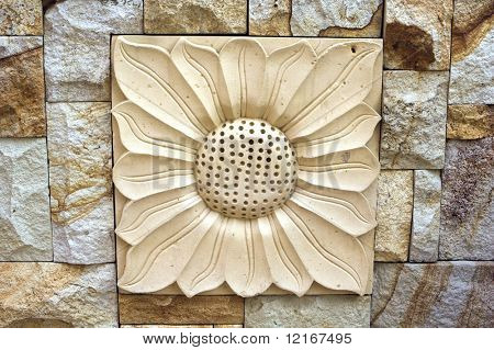detail of sunflower chiseled in limestone