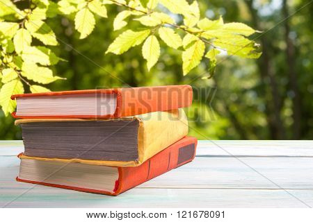 Stack of colorful books on wooden table on natural blurred backg